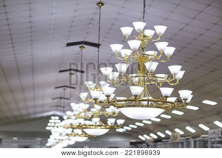 Chandelier in the hall. Golden chandelier with white lamps in the room.