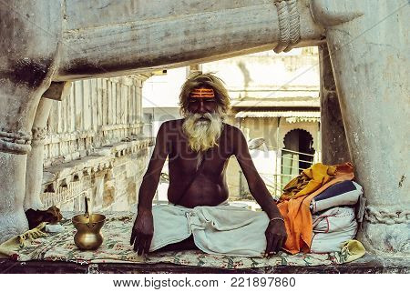 Old sadhu sitting in the lotus position in one of the temples of Udaipur, India in october 2014
