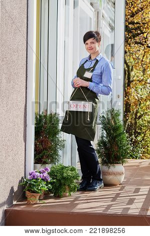 Woman holding small business.A smiling florist stands in the doorway of the store holding an open sign.Shot from an attractive saleswoman standing at the doorway in the open air in a green apron.