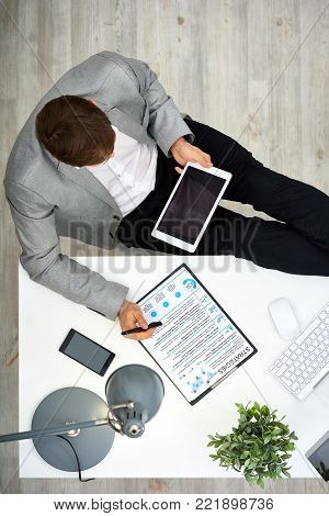 Busy young manager in formalwear sitting at office desk and using digital tablet while wrapped up in preparing visual presentation, directly above view