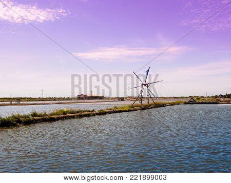 wind turbine in Salt evaporation pond on blue sky with cloud background