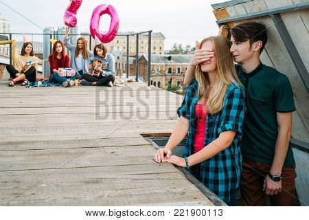 20th birthday surprise. Boy covering girl's eyes. Rooftop party with friends