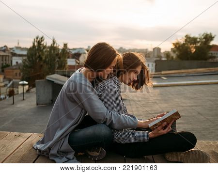 Couple sits on a roof top reading a book. Literature self-improvement, leisure, hobby, bookworms concept
