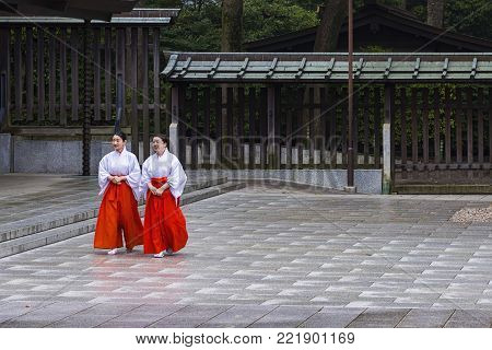 Tokyo, Japan - April 21, 2014: View of two Mikos in Meiji Shrine. In Shinto, a miko  is a shrine maiden or a supplementary priestess trained to perform sacred tasks