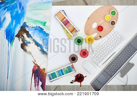 Workplace of talented artist: directly above view of desktop with colorful painting, gouache and wax crayons, no people