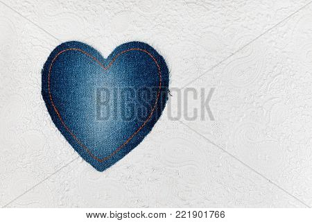 Classic heart made of denim lies on the embossed white skin. Space for text. View from above