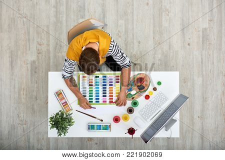 Talented young artist at work: he sitting at office desk and thinking over his new masterpiece, directly above view