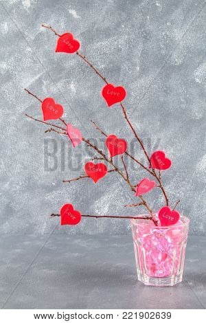 Red hearts with an inscription Love hang on branches on a gray concrete background. Love tree. The concept of Valentine's Day. A symbol of love