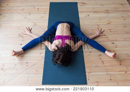 Top view of female yogi doing advanced kurmasana tortoise pose on mat indoors while practicing yoga.