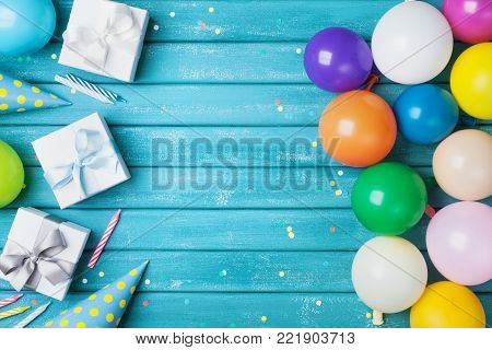 Birthday party banner or background with colorful balloon, gift, carnival cap, confetti and candy. Copy space.