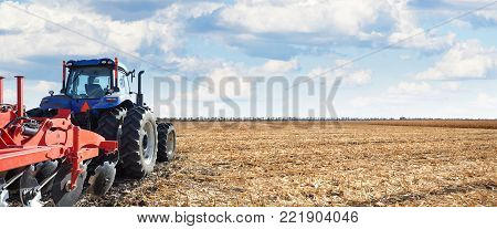Tractor working on the farm, fertile land, tractor on cloudy sky background, cultivation of land, agricultural machine