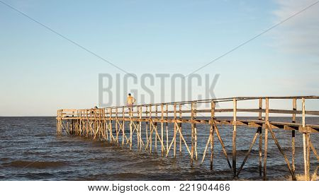 horizontal image of a young man walking across a long wooden pier out over the lake on a warm summer evening.