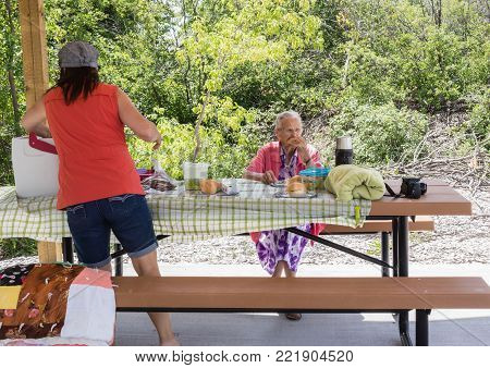 horizontal image of an elderly mother and daughter having a picnic lunch on a warm summer sfternoon.