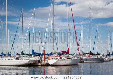 horizontal close up of a fleet of docked sail boats on the water close to shore on a bright sunny summer day.