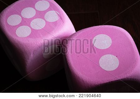 horizontal macro image of two large pink dice with white dots.