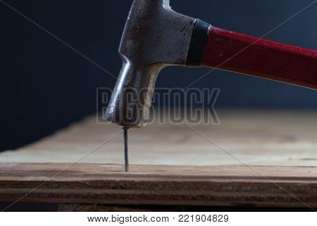 The carpenter uses a hammer to hit the nail on the wooden floor.