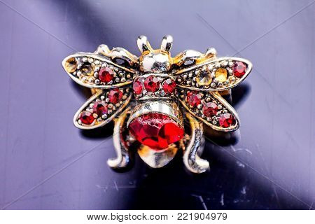 Vintage brooch in the form of bees (or fly or bug) made of beads, fabric and crystals, clipping on a old black background