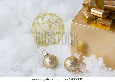 horizontal image of a gold box with a shiny gold bow on top with wire shaped ball and two small gold balls lying beside it on a white fluffy background.