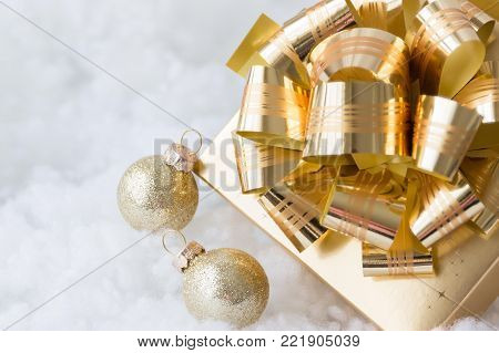 horizontal image of a gold shiny Christmas bow on top of a box with two small gold balls lying beside it on white fluffy background.