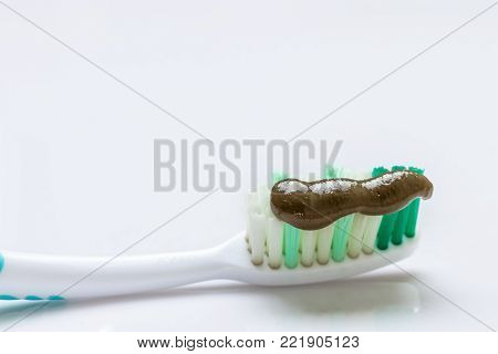 Squeeze herbal toothpaste with black on the toothbrush.