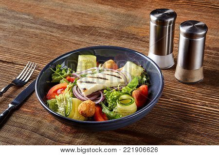 Fried Tofu Salad with Cucumbers, Tomatoes, Avocado and Sesame Seeds. Homemade asian vegetable and tofu salad in ceramic bowl on wooden background. Healthy asian diet vegan vegetarian salad food.