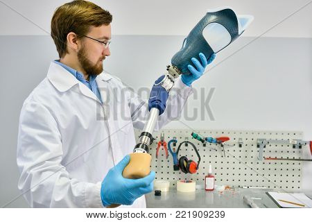 Portrait of young  prosthetics technician holding prosthetic leg  checking it for quality and making adjustments while working in modern laboratory, copy space