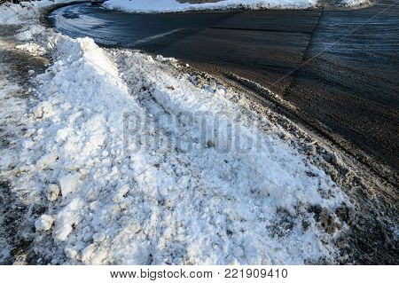 Winter road on curve with snow plowed and sunshine, conceptual winter driving, curvy street car safety snow on streets black ice and slippery road background photography with room for copy