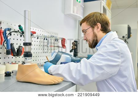 Side view portrait of  young prosthetics technician  making prosthetic leg at desk in office and writing notes, copy space