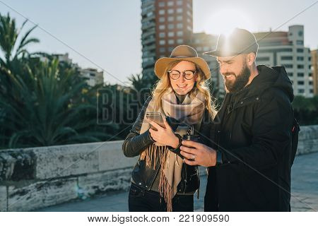 Couple of young travelers are standing on city street and using smartphone, holding cups of coffee.Girl shows guy an image on smartphone screen.Friends are walking around city.Lifestyle, social network.