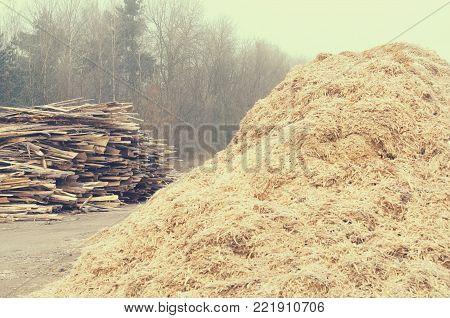 Waste sawmill in the form of a stack of boards and a mountain of sawdust