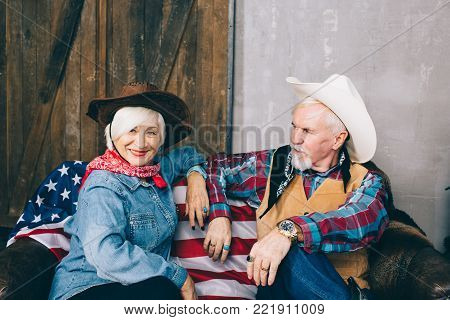 elderly couple dressed in cowboy style, sitting on a sofa with an American flag. To celebrate America's Independence Day