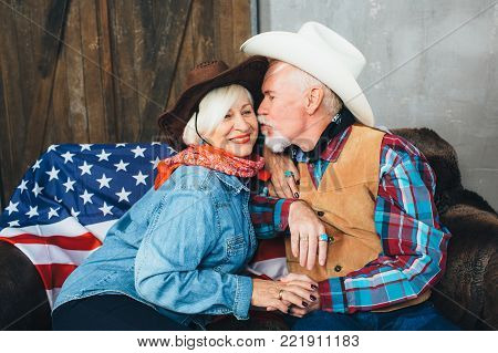 elderly couple, dressed in cowboy hats, smiling, taking each other's hands. Behind, on the couch lies the American flag, the celebration of America's Independence Day