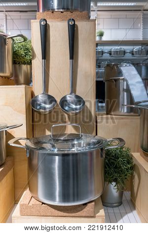 Essential kitchenware display. Stainless steel cooker and soup ladles against wooden background over countertop.