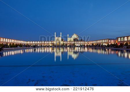 Isfahan, Iran - April 23, 2017: Evening view of Naghsh-e Jahan Square with Shah mosque and  shopping arcades at night illumination, which are reflected in  water of decorative fountain pond.