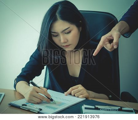 Female office worker is working under pressure from supervisor