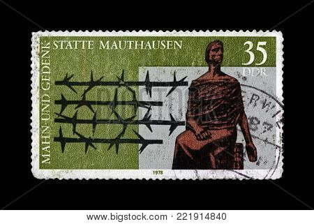 DDR - CIRCA 1978: vintage canceled stamp printed in DDR shows Mauthausen concentration camp Memorial, barbed wire, circa 1978. vintage postal stamp isolated on black background.