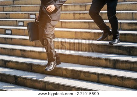 young handsome business man holding briefcase and walking fast down stairs going to work time at morning in the city, determination, confidence, lifestyle, rush hour, grow up and successful concept