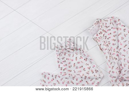 Pants and jacket on white wooden background. Nightwear set with flower pattern. Stylish and comfy clothing for girls.