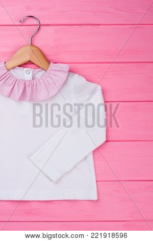Adorable blouse for baby girl on wooden hanger. White top decorated with pink ruffle collar. Kids fashion.