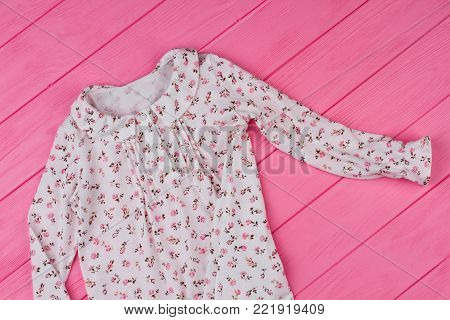 Nightgown for little lady, pink wooden background. Ruffle collar and floral pattern. Stylish sleepwear for girls.