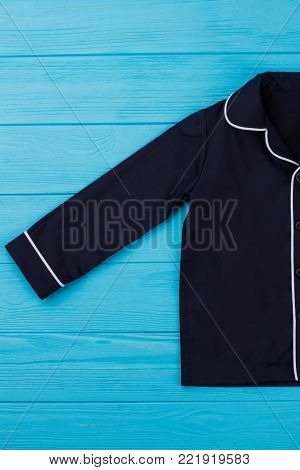 Navy shirt with white edging on cuffs and collar. Boys pajama's top on blue wooden background.