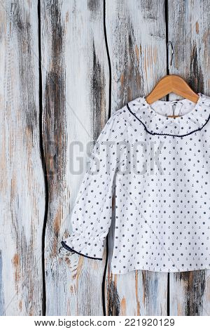 Girls' top on wooden hanger. Ruffle collar and cuffs, white blouse decorated with nautical pattern. Sleepwear for kids.