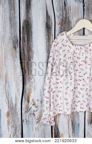 Long sleeve top on hanger, wooden rustic background. Pleasant floral print and ruffles. Stylish nightwear for teenage girls.