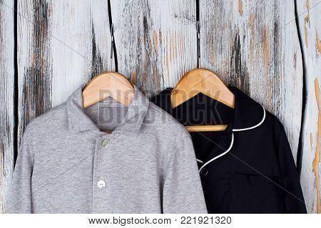 Jackets on wooden hangers. Gray melange and navy pajama tops. Boys wardrobe, sleepwear and loungewear.