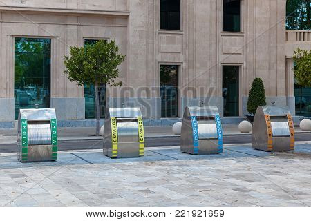 Palma de Mallorca, Spain, garbage cans of four kinds on the background of the building. Trash bins in Spain.