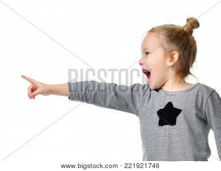 Young girl kid surprised yelling shouting pointing finger at the corner  isolated on a white background