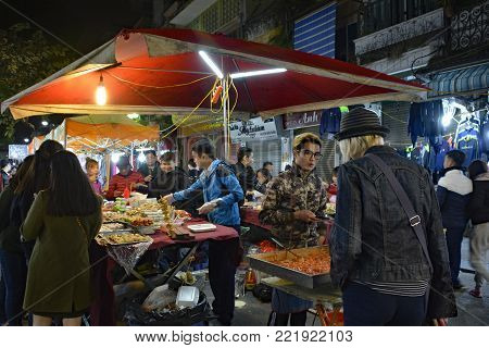 Hanoi, Vietnam - December 15th 2017. A young man serves customers at a night market stall selling local foods in the historic old quarter of Hanoi