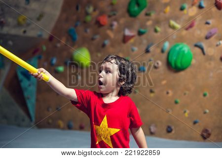 The boy is on the climbing wall. The child with a stick shows climbing routes in a rock climbing gym. A small athlete. Active lifestyle.