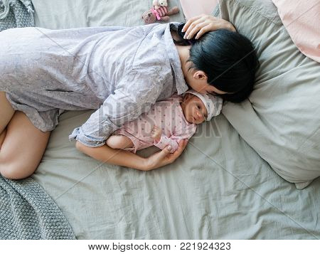 a mother's daytime sleep with her newborn baby. tired but happy. family values.