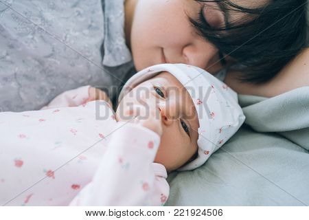 Mom with pleasure sniffing her newborn baby. tenderness and love. happy motherhood. poster